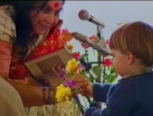 un bambino offre un fiore a Shri Mataji